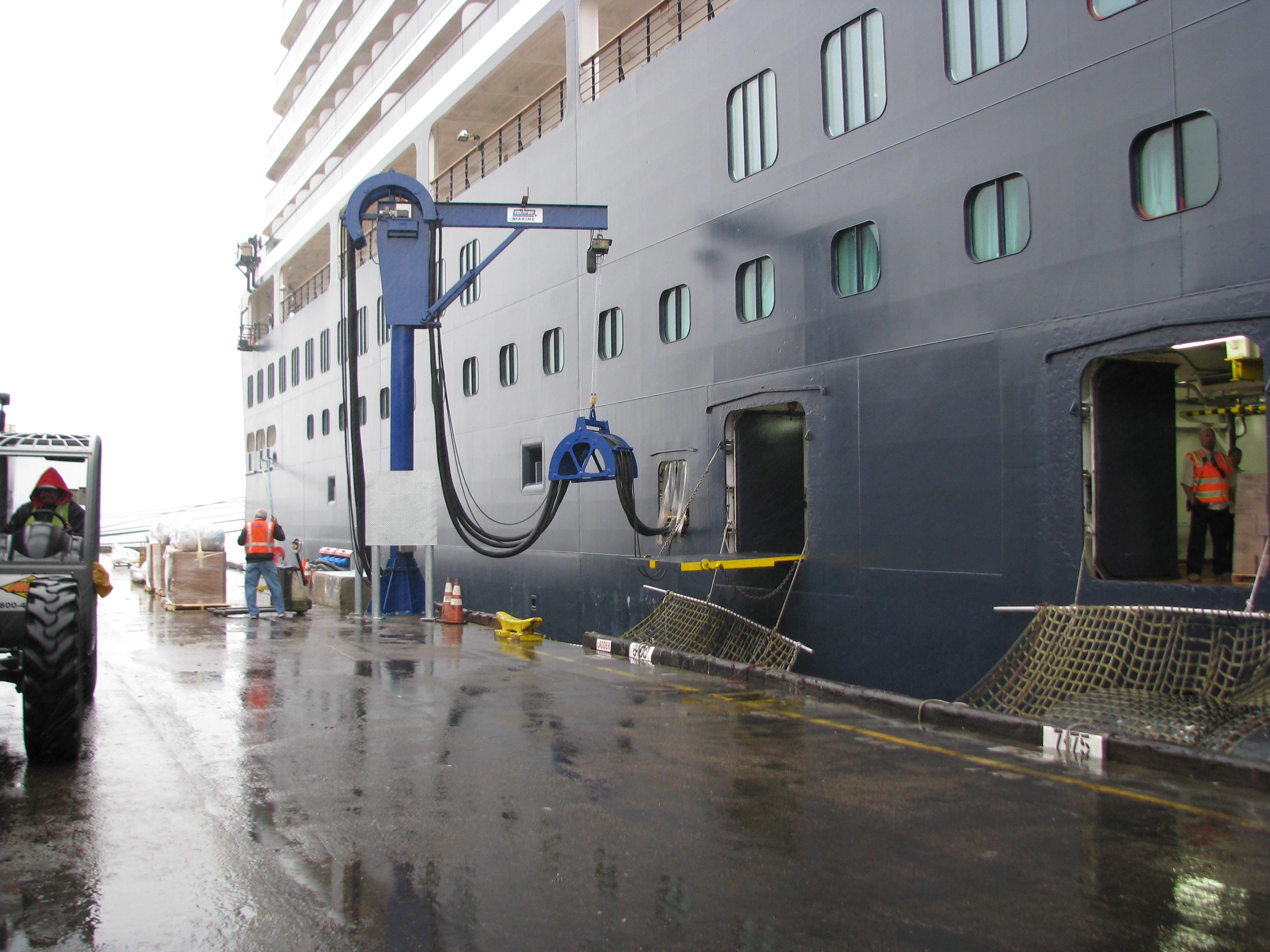 Hier zien we walstroom in actie in San Diego: een kraan met stroomleidingen voert elektriciteit het schip in.